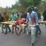 A beheaded corpse being carried away