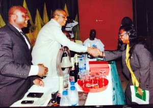 Gertie Njar, the only female inductee receives a handshake from Dep. Gov, Ivara Esu at the induction